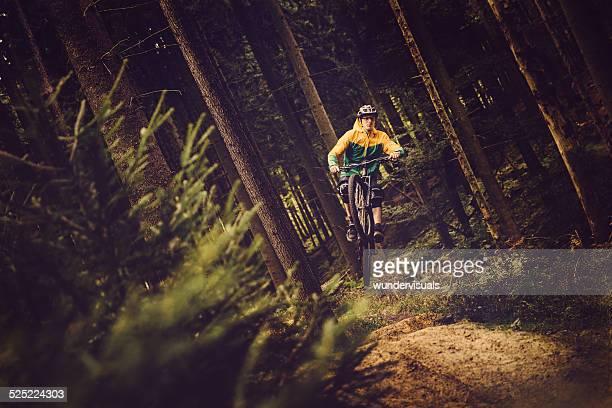 Mountain Biker springt im Wald