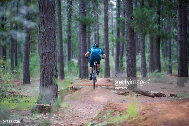 mountain biker jumps over a technical jump - cross country cycling stock pictures, royalty-free photos & images