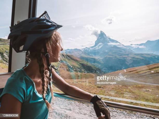 mountainbiker blickt aus sonnigem zugfenster, matterhornblick - pinnacle peak stock-fotos und bilder
