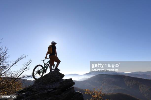 Mountain biker looks out to mountain ranges and wind turbines