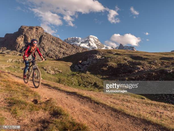mountain biker on dirt trail, switzerland - pinnacle peak stock pictures, royalty-free photos & images