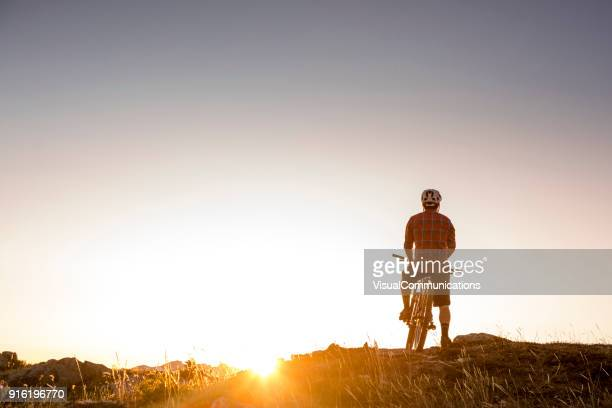 mountain biker on top of mountain. - escapism stock photos and pictures