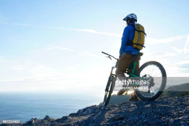 Mountain biker pauses on cliff above sea, hills