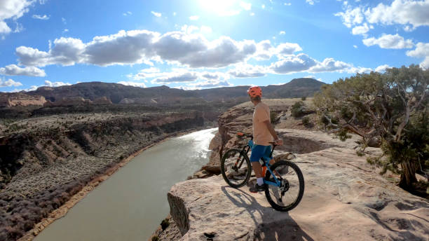 Mountain biker pauses on edge of canyon overlook