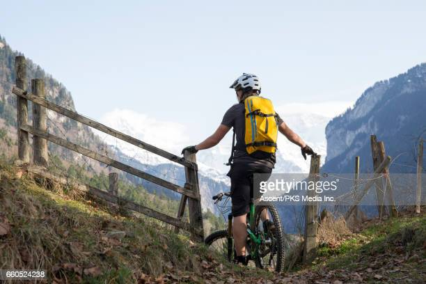 mountain biker pauses on mountain trail beside fence, looks off - bern stock pictures, royalty-free photos & images
