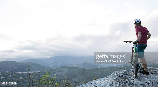 Mountain biker pauses on rock prow above valley