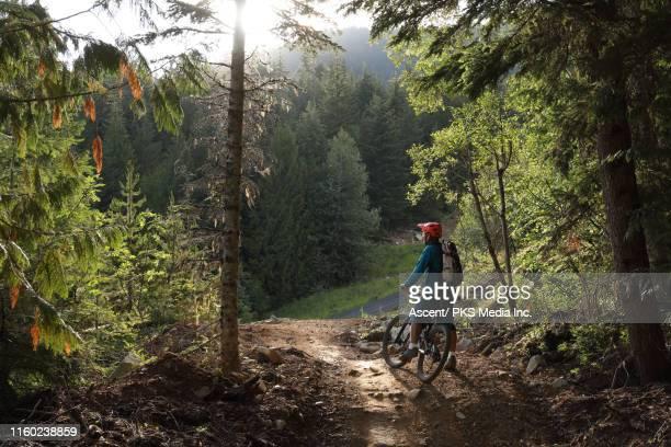 mountain biker pauses on trail to enjoy view - mountain biking stock pictures, royalty-free photos & images