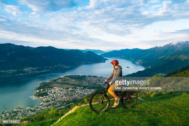 Mountain biker pauses to enjoy view over mountains, lake