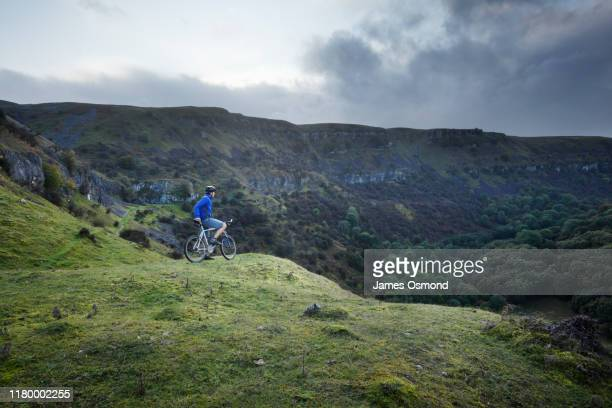 a mountain biker pausing to take in the view from the llangattock escarpment. - bicycle stock pictures, royalty-free photos & images