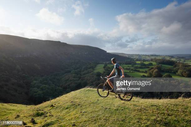 a mountain biker pausing to take in the view from the llangattock escarpment. - riding stock pictures, royalty-free photos & images