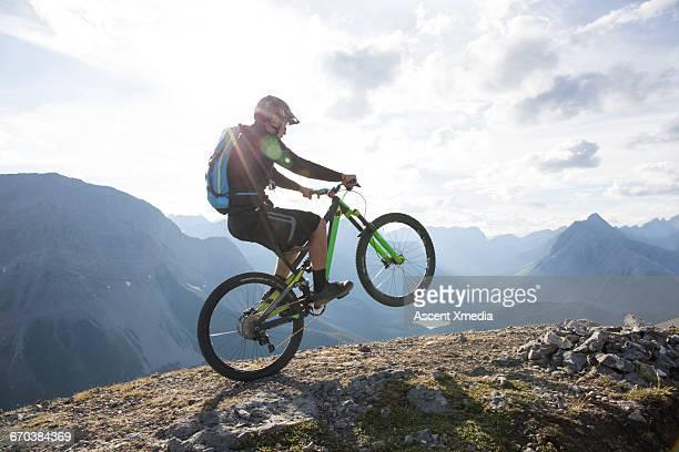 mountain biker pops wheelie on ridge crest - attrezzatura sportiva foto e immagini stock