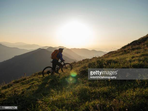 mountain biker pushing his bicycle to the mountain peak. - active lifestyle stock pictures, royalty-free photos & images