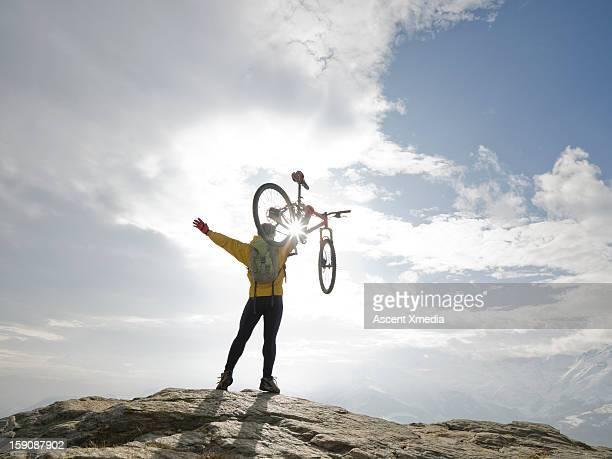 Mountain biker raises bike overhead, arms out