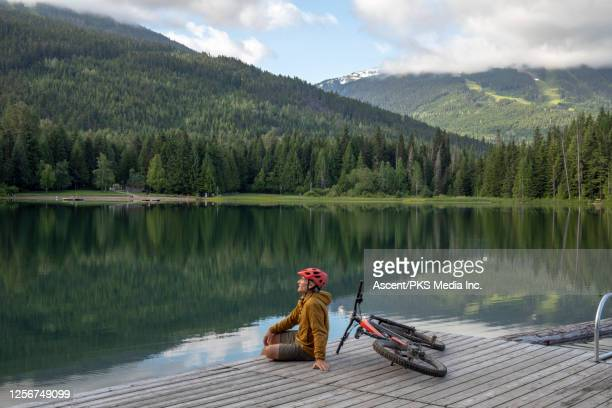 Mountain biker relaxes on lake pier, sunrise