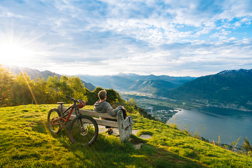 Mountain biker relaxes to enjoy view over mountains, lake - gettyimageskorea