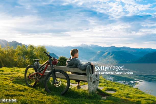 Mountain biker relaxes to enjoy view over mountains, lake