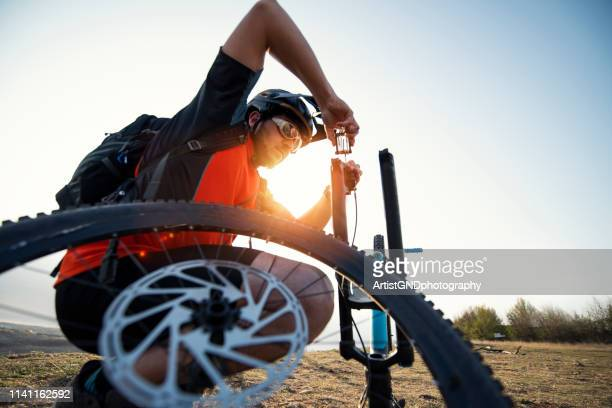 mountain biker repairing his bicycle fork and brake with tools. - air pump stock photos and pictures