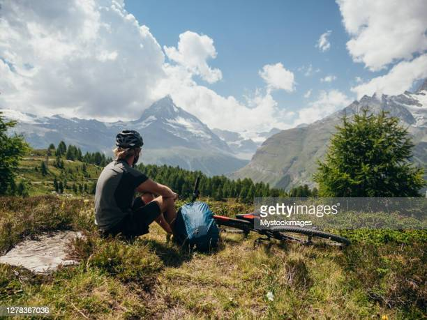 mountain biker resting on grass area - zermatt stock pictures, royalty-free photos & images