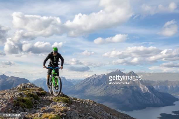 mountain biker rides along mountain ridge in the morning - sport venue stock pictures, royalty-free photos & images