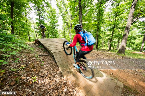 mountain biker rides at slaughter pen in bentonville, arkansas - bentonville stock pictures, royalty-free photos & images