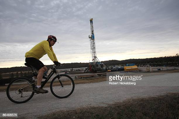 Mountain biker rides by a 150-foot derrick positioned over a natural gas well site along a Trinity River embankment on December 20, 2008 in Fort...