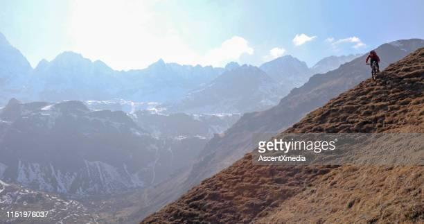 mountain biker rides down grassy mountain trail - forza italia foto e immagini stock