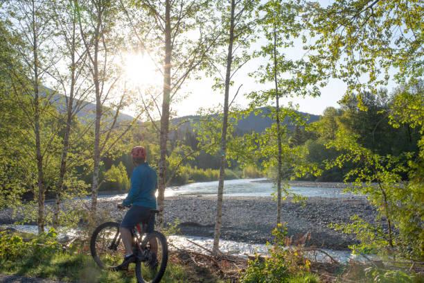 Mountain biker rides his e-bike above mountain river