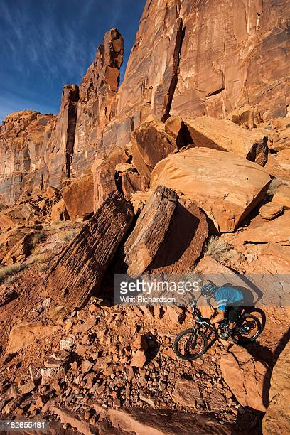 a mountain biker rides on a technical trail in a rocky desert scene. - moab utah stock pictures, royalty-free photos & images