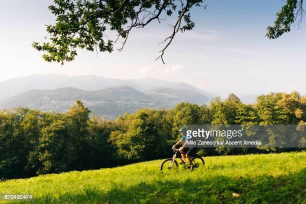Mountain biker rides through meadow above valley, mountains