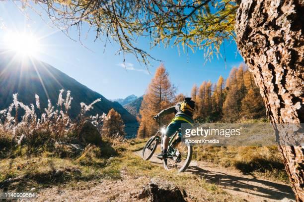 mountain biker rides up grassy slope - mountain bike foto e immagini stock