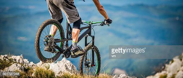 mountain biker riding across rocks on a moutain - mountain bike stock pictures, royalty-free photos & images