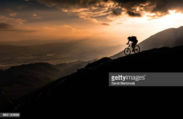 a mountain biker riding down a ridge line at sunset. - マウンテンバイク ストックフォトと画像