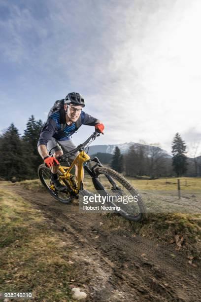Mountain biker riding down hill on single track, Bavaria, Germany