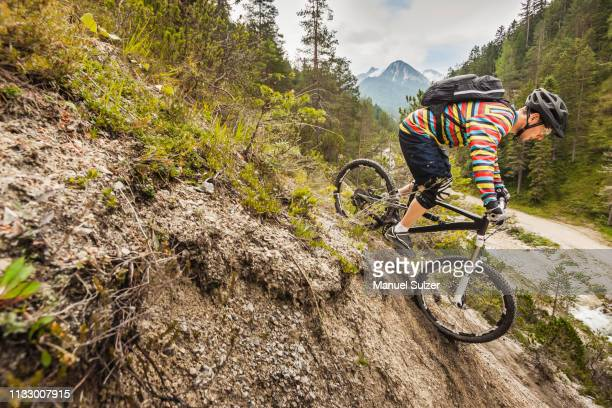 mountain biker riding down mountain - downhill skiing stock pictures, royalty-free photos & images