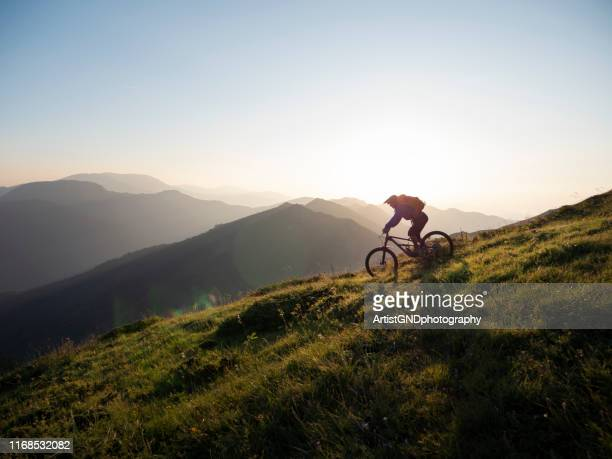 mountain biker riding downhill - outdoor pursuit stock pictures, royalty-free photos & images