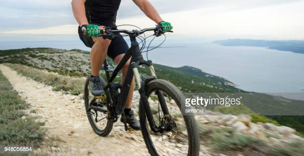 mountain biker riding mountain bike - green glove stock photos and pictures