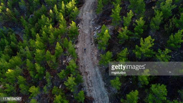 mountain biker riding on a dirt road aerial view - ecchi biker stock pictures, royalty-free photos & images