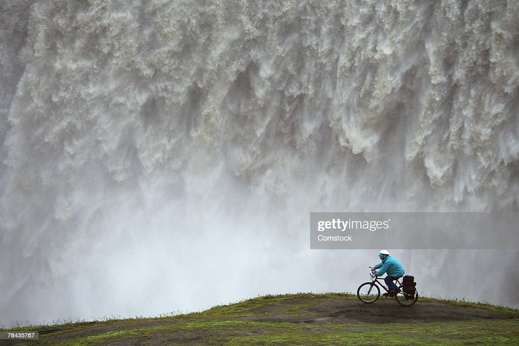 Mountain biker riding on ridge next to waterfall : Stockfoto