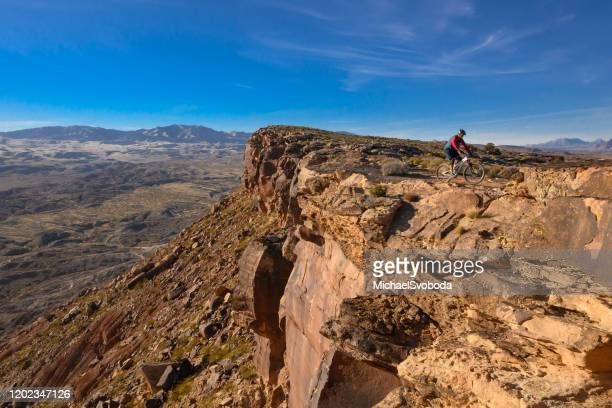mountain biker riding the southwest desert on a bluff - st. george utah stock pictures, royalty-free photos & images