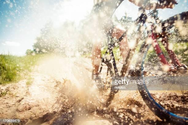 mountain biker Reiten durch ein schmutziges Pfütze