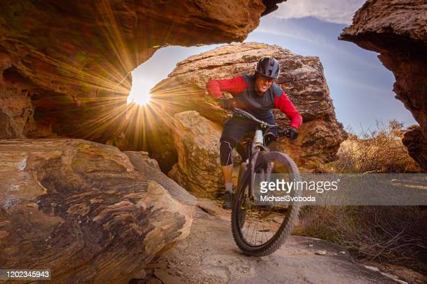mountain biker riding through boulders in the southwest desert - cross country cycling stock pictures, royalty-free photos & images