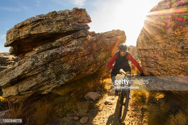 mountain biker riding through boulders in the southwest desert - st. george utah stock pictures, royalty-free photos & images