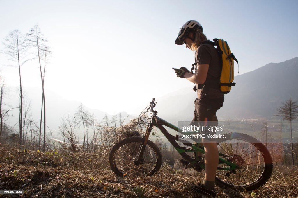 Mountain biker sends text from forest track, mountains : Stock Photo