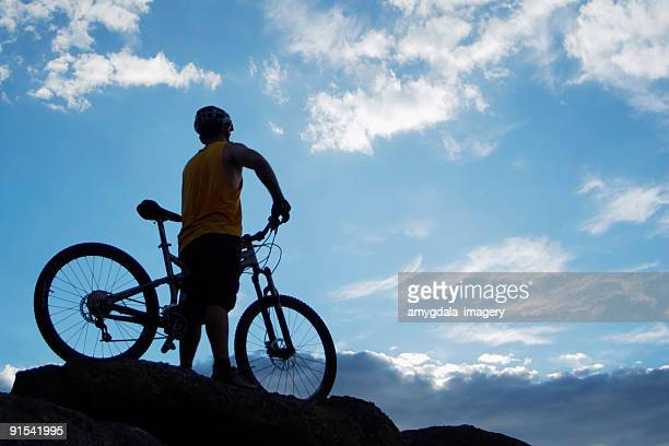 mountain biker silhouette with blue sky clouds