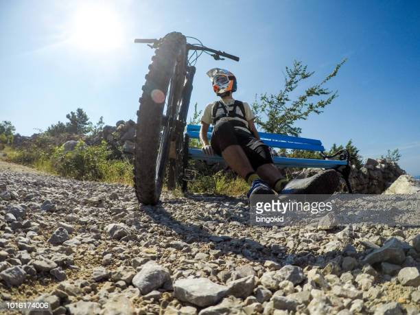 Mountain biker sitting and resting on hot day
