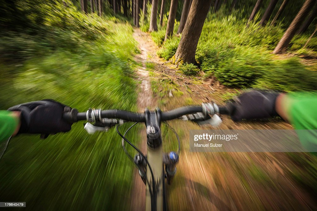 Mountain biker speeding down forest path : Foto de stock