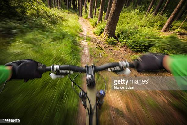 Mountain biker speeding down forest path