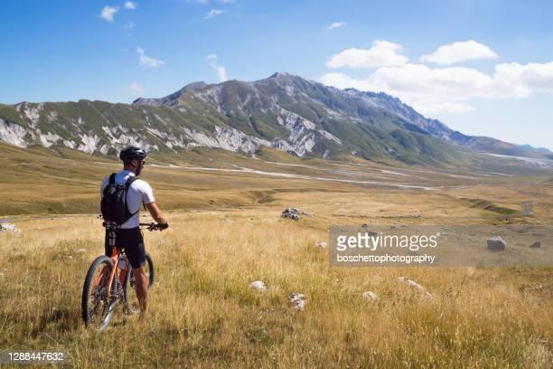 マウンテンバイカーは、パノラマの景色を楽しむ彼のバイシクルと山道に停止しました - カンポ・インペラトーレ ストックフォトと画像