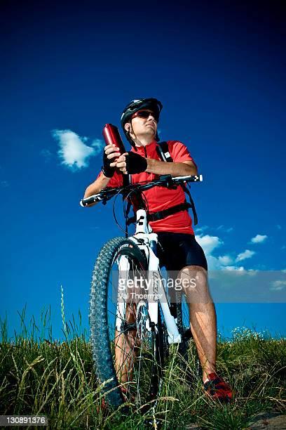 Mountain biker taking a break, holding water bottle
