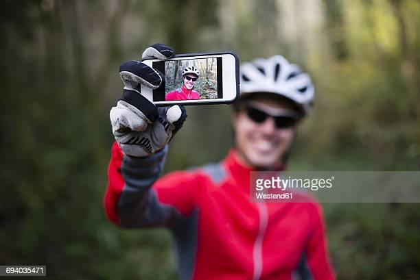 mountain biker taking selfie with his smart phone - fotohandy stock-fotos und bilder